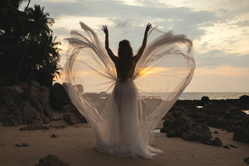 Silhouette of bride wearing beautiful wedding dress on the beach