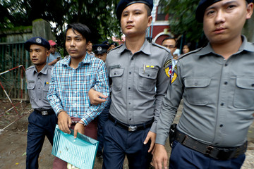 Detained Reuters journalist Kyaw Soe Oo is escorted by police officer as he leaves the Insein court in Yangon