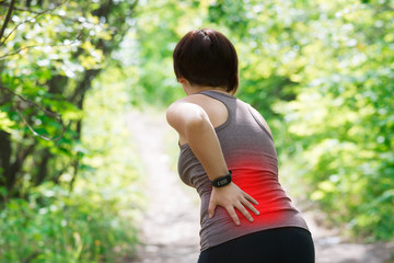 Woman with back pain, kidney inflammation, injury during workout