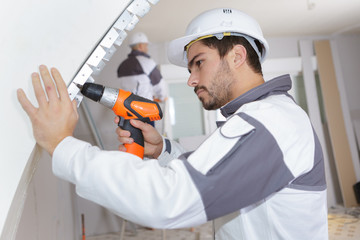 young man drilling the wall with drill perforator