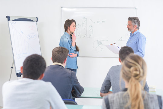 young woman writing on white board during class
