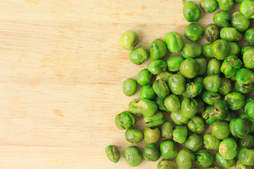 green peas on plate and wooden
