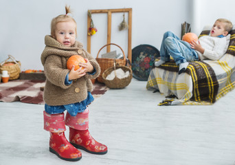 Beautiful little girl with pumpkin in hands, big boots and a warm sweater.