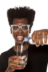 Portrait of young african american man pouring water from plastic bottle in a glass on white background