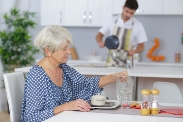 cheerful young man serving breakfast to an elderly woman