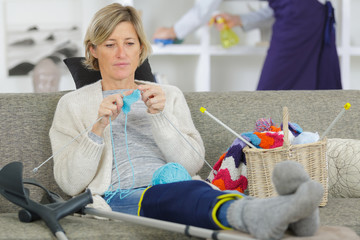 cheerful injured woman knitting on the sofa