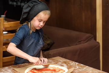 Little girl cook in uniform prepares pizza in the kitchen.
