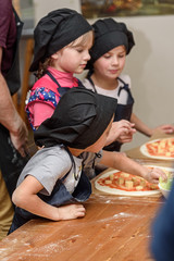 Pizza, children and the concept of cooking - children make pizza.