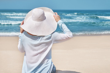 Summer beach concept. Woman in big hat on idyllic beach. White sand, blue sky and crystal sea