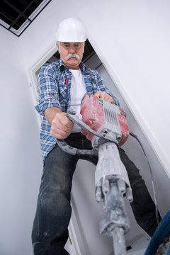 Senior man using jackhammer