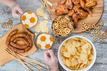 Group of friends holding glass mugs  of beer with a soccer ball on a beer foam  on wooden background with snacks. Top view