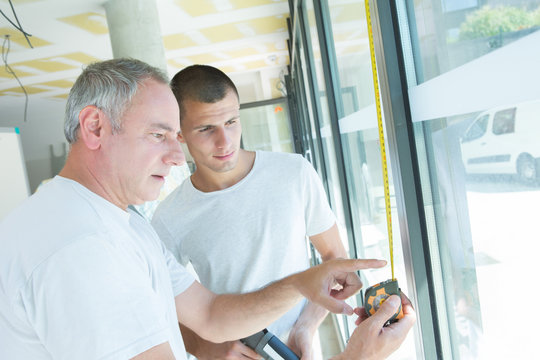 Men measuring window