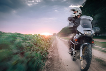 Biker Man Riding on Adventure Motorcycle, summer sunset, sun rise, off road travel concept, enduro rider, freedom and active lifestyle
