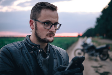 close up portrait of a handsome young man in glasses and leather jacket and gloves, uses a smartphone, a concept of help and support on the road, while traveling, motorcycle on backgroud