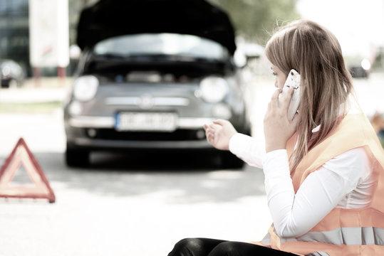 Junge Frau hat eine Panne mit ihrem Auto