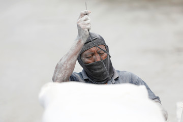 A worker stitches a sack of kaolin powder after unloading it from a wooden ship at Sunda Kelapa harbour in Jakarta