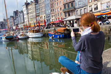 girl taking a shot of Honfleur harbor