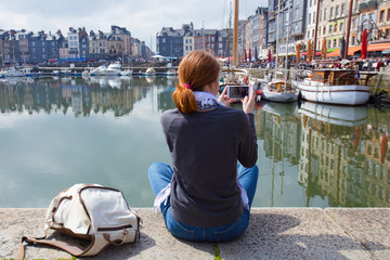 girl taking a shot of Honfleur harbor