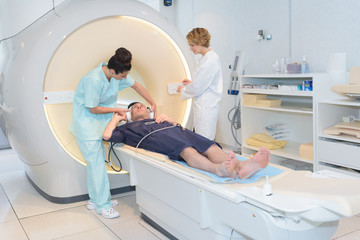 Nurse putting ear protectors on patient for mri scan