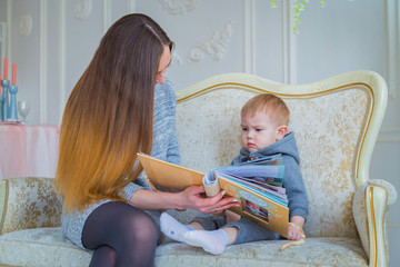 Young mother and her baby son sitting on the couch and looking photobook togerher at home