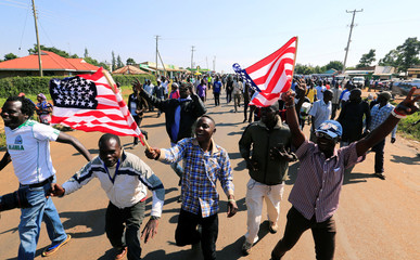 Residents wave the U.S. national flag as they chant slogans on the road ahead of the visit by Former U.S. President Barack Obama to his ancestral Nyangoma Kogelo village in Siaya county