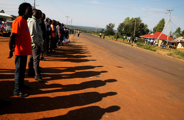 Residents wait on the road ahead of the visit by the former U.S. President Barack Obama to his ancestral Nyangoma Kogelo village in Siaya county