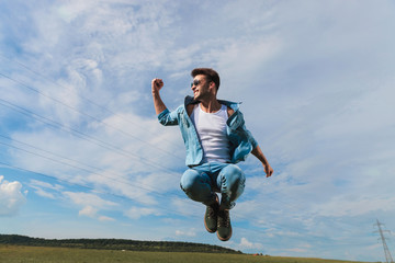 joyful casual man jumping and celebrating outside