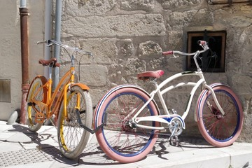 Two retro bicycles parked against a stone wall in a medieval village. This mean of transport became a symbol for the ecologists.