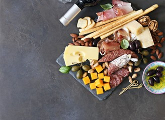 Mediterranean appetizers. Platter with tapas selection: jamon, cheese variety, olives and nuts.   Overhead view, copy space.