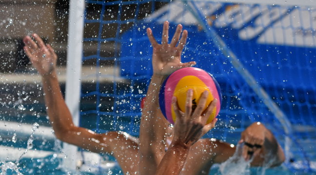 Hand tree on a waterpolo match. Players with goalkeepr defend against shooting.