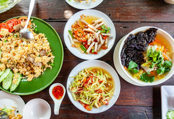 Group of Food Som Tam,Tum Lai Bua or Lotus Root Salad, Pork Stir Rice and Seaweed Soup with Pork on Wood Table.