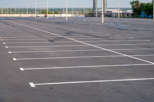 A deserted parking lot with crowds in the middle against the background of the blue cloudy sky.