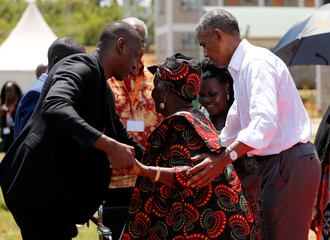 Former U.S. President Barack Obama assists his grandmother Sarah Obama at the Sauti Kuu resource centre near his ancestral home in Nyangoma Kogelo village in Siaya county