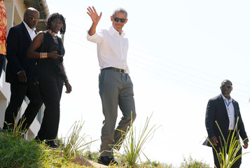 Former U.S. President Barack Obama waves to photographers as he tours the Sauti Kuu resource centre near his ancestral home in Nyangoma Kogelo village in Siaya county