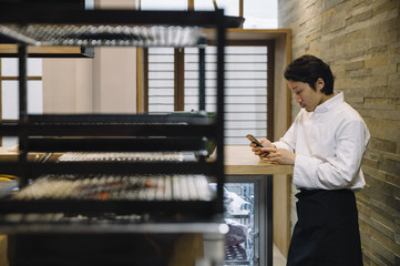 Asian chef using smartphone in kitchen