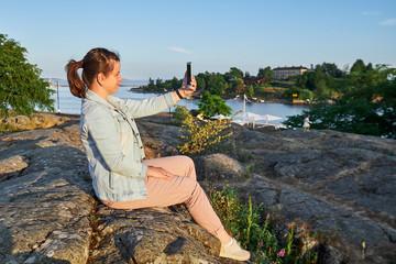 woman taking a selfie. Finland, Helsinki, Kaivopuisto park