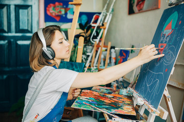 Young beautiful woman drawing something on  canvas and listening music,sitting  in art studio .