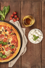 Pepperoni pizza closeup with white wine, ingredients, and place for text