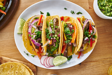 Wall Mural - tasty mexican tacos with beef fajita filling served with salsa and guacamole in flat lay composition