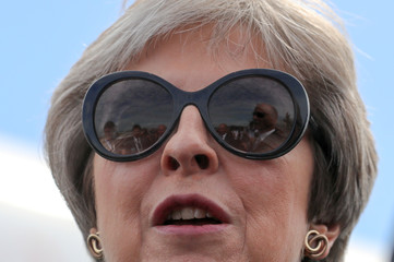 British Prime Minister Theresa May reacts to a flypast at the Farnborough Airshow, in Farnborough