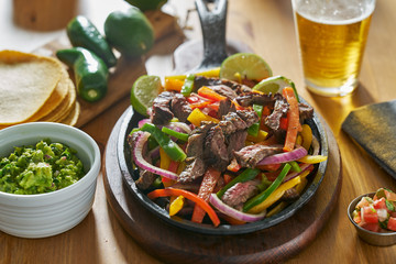 Wall Mural - mexican beef fajitas in iron skillet with guacamole and beer