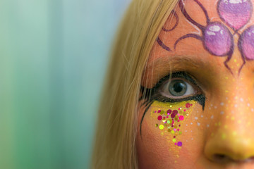 Attractive girl with a painted face. Aquagrum on the face of a woman.