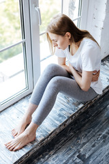 Feeling bad. Unhappy slim woman sitting on the windowsill and having a stomachache