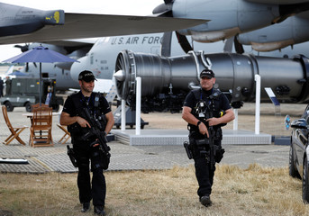 British armed police officers patrol amongst U.S. military aricraft at the Farnborough Airshow, in Farnborough