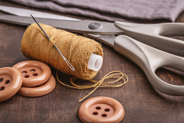 On  brown wooden surface are objects for sewing.