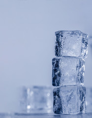 Ice cubes covered with drops of water stand on top of each other. Frozen water in form of a cube, ice. Critically pure ice.