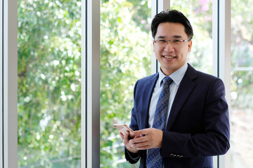 Asian Businessman holding smart phone with happy smiling face standing by windows, inside eco office building background, businessman on smart phone
