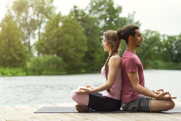 Woman and man practicing yoga in nature. Couple meditation. Copy space