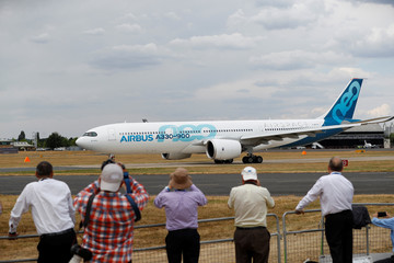 Spectators look at an Airbus A330neo at the Farnborough Airshow, in Farnborough