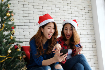Two young cute asia women holding smartphone and credit card while shopping online with happiness, Christmas holiday shopping concept